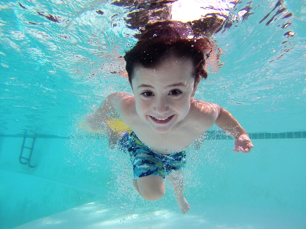 boy swimming for blog about the risks of owning a swimming pool
