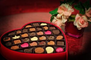 Picture of flowers and chocolates for blog about Valentine's Day Health Hazards