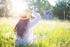 Woman wearing hat sitting in grass during spring to accompany article Avoiding Springtime Injuries